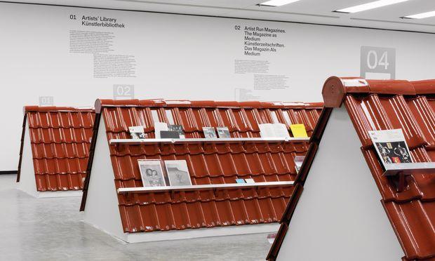 Drei Ziegeldächer dienen in der Kunsthalle als Regale für Hunderte Kunst-Publikationen. Überfliegen wäre eine Assoziation dazu.