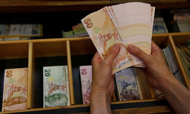 A money changer counts Turkish lira banknotes at a currency exchange office in Istanbul