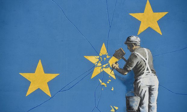 A section of an artwork attributed to street artist Banksy, depicting a workman chipping away at one of the 12 stars on the flag of the European Union, is seen on a wall in the ferry  port of Dover