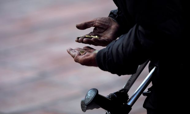A beggar counts coins as he asks for alms during the International Day for the Eradication of Poverty in downtown Malaga