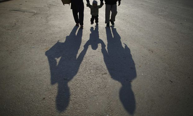 The shadow of a family is cast on the road as they walk along the deserted road while heading towards work during the general strike in Kathmandu