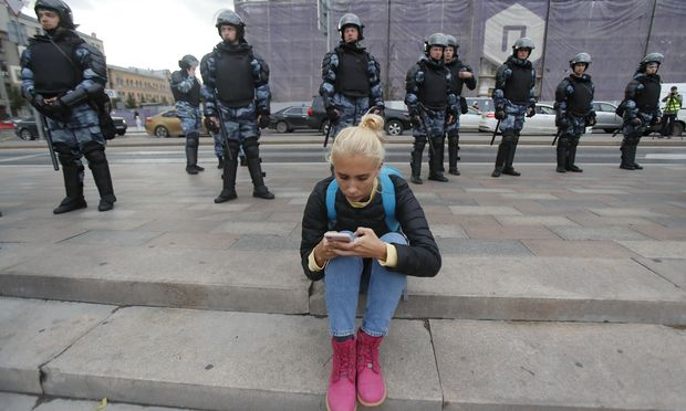 Law enforcement officers stand guard after a rally to demand authorities allow opposition candidates to run in a local election in Moscow