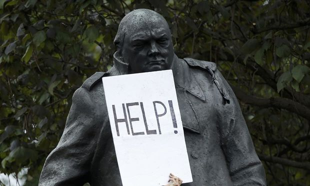 A demonstrator holds a placard that reads 'Help!' against a statue of Winston Churchill during an anti-austerity protest in central London