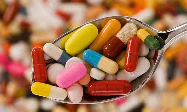 Auf einem Loeffel liegen Tabletten
