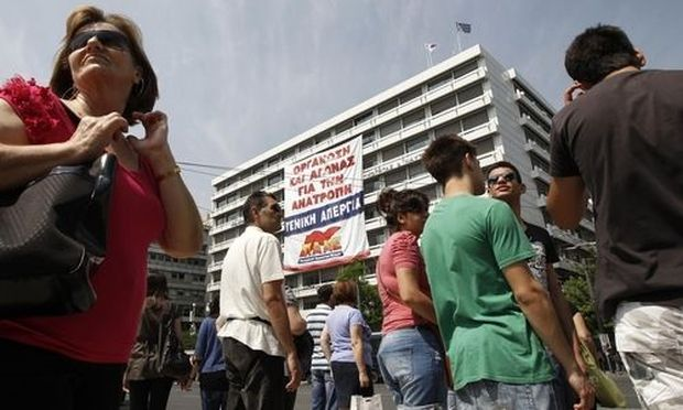 A huge banner, unfolded by the Greek Communist-affiliated trade union PAME, is hung from the Greek Fi