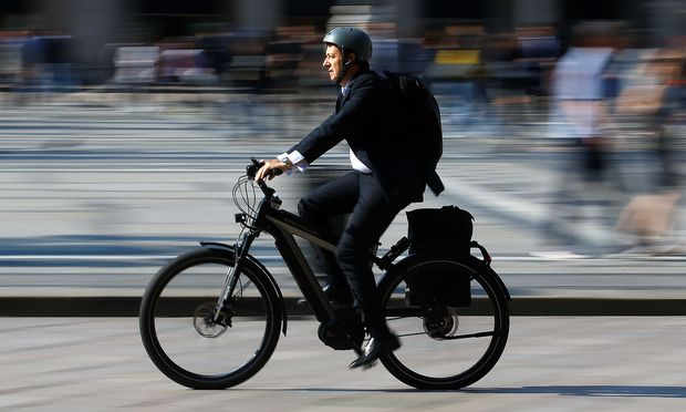 A man rides an electric bicycle, also known as an e-bike, in downtown Milan
