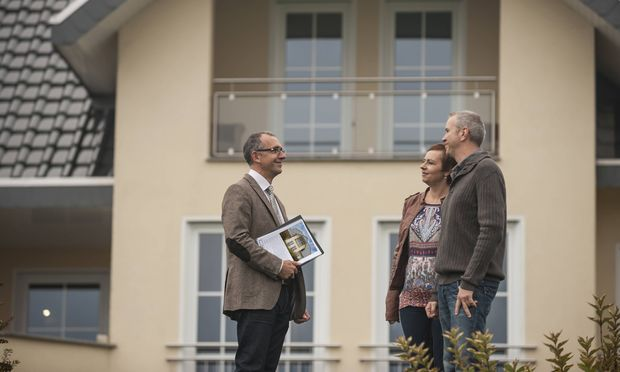 Estate agent communicating with potential buyers in front of residential house model released Symbol