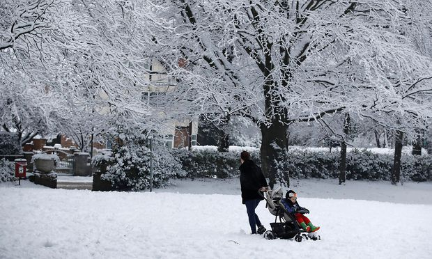Man drags his child in a baby carriage in Manchester