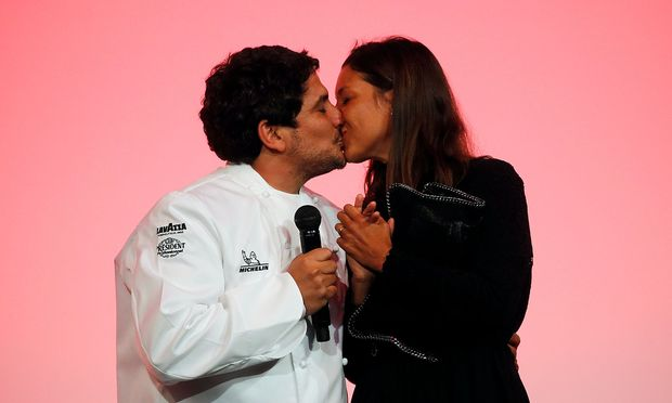 Newly awarded three-star Michelin Chef Mauro Colagreco, for his restaurant Mirazur in Menton, kisses his wife on stage  during the Michelin Guide 2019 award ceremony in Paris