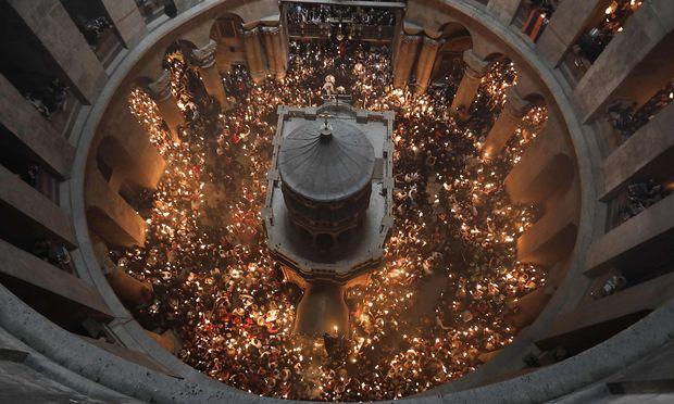 """Bei der orthodoxen Zeremonie des """"Heiligen Feuers"""" wird das wundersam entzündete Licht in der Grabeskirche weitergegeben."""
