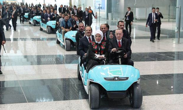 Turkey's President Tayyip Erdogan drives an airport golf cart with his wife Emine Erdogan and officials during the official opening ceremony of Istanbul's new airport in Istanbul