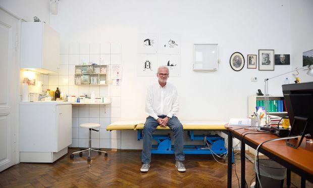 Hugo Gold in seinem Sprechzimmer. Die Wände zieren Comics von Zeichner Bernd Püribauer, Porträts der Ärzte seiner Familie. Urgroßvater Urgroßonkel und Großvater.