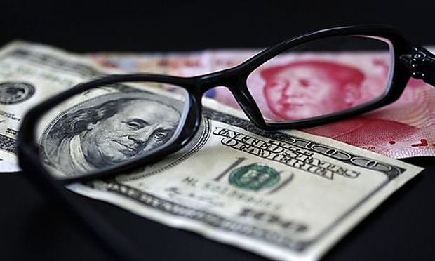 A U.S. dollar note and a Chinese yuan banknote are seen through a pair of spectacles in this picture