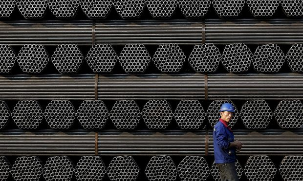 File photo of a worker walks past a pile of steel pipe products at the yard of Youfa steel pipe plant in Tangshan in China's Hebei Province