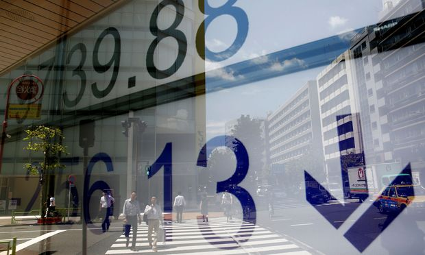 People are reflected on an electronic board showing Japan's Nikkei average outside a brokerage at a business district in Tokyo