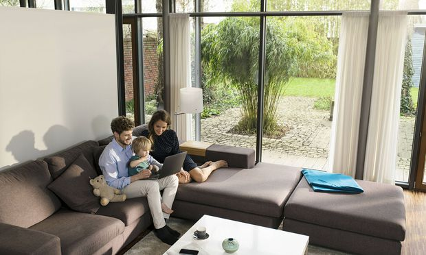 Parents and son sitting on sofa in modern living room using laptop at home model released Symbolfoto