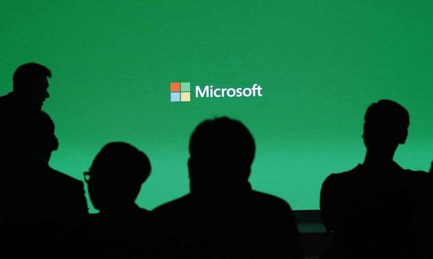 People attend a presentation of the Xbox One by Microsoft as part of ChinaJoy 2014 in Shanghai