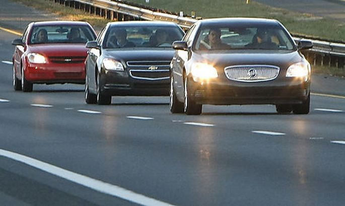 General Motors CEO Richard Wagoner, second vehicle passenger seat, travels in a three-car convoy with