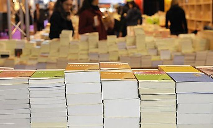 Books are displayed during the installation of the annual Paris Book Fair