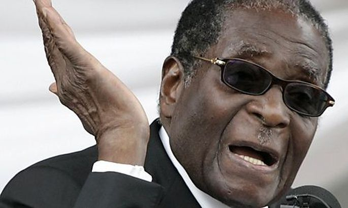 Zimbabwes President Robert Mugabe addresses mourners during the burial of ZANU-PF political commissas President Robert Mugabe addresses mourners during the burial of ZANU-PF political commissa