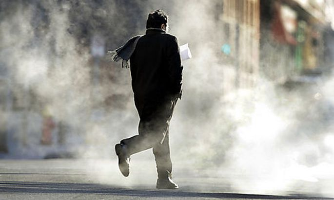 A man hurries across a chilly street as steam rises from below Tuesday, Jan. 5, 2010, in St. Louis. B