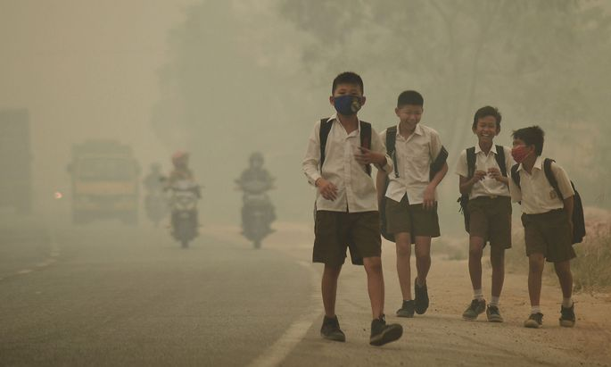 Students walk along a street as they are released from school to return home earlier due to the haze in Jambi