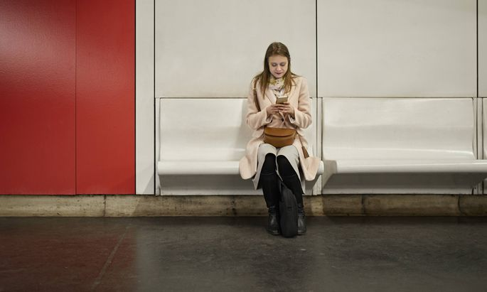 Austria Vienna young woman waiting at underground station using smartphone model released Symbolfo