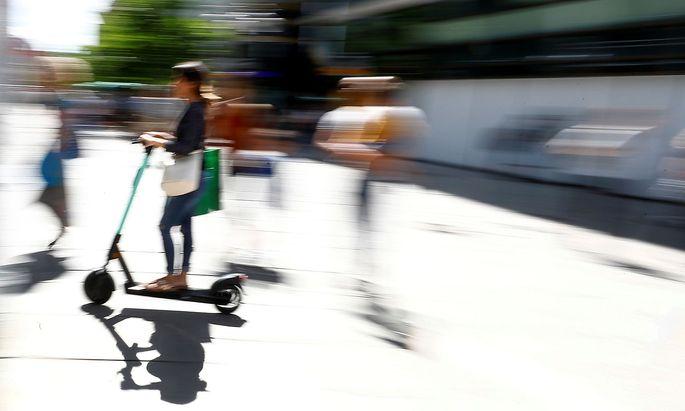 A young woman rides an e-scooter through a pedestrian area in Frankfurt