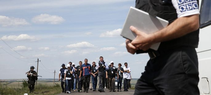 Monitors from OSCE and members of a forensic team visit the crash site of Malaysia Airlines Flight MH17 near the village of Hrabove