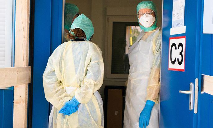 Hinter der Schiebetür stehen zwei Frauen in kompletter Schutzmontur, wie man sie aus Katastrophenfilmen kennt (Symbolbild).