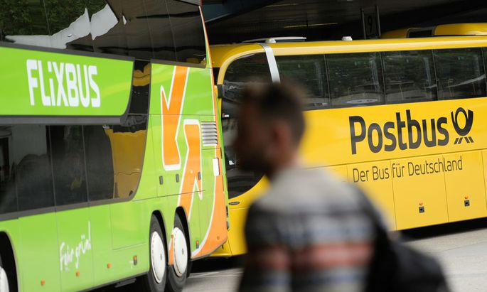 A man walks near Flixbus and Postbus busses at the main bus station in Berlin