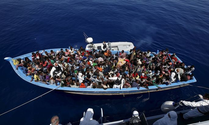 A group of 300 sub-Saharan Africans sit in board a boat during a rescue operation by the Italian Finance Police vessel Di Bartolo off the coast of Sicily