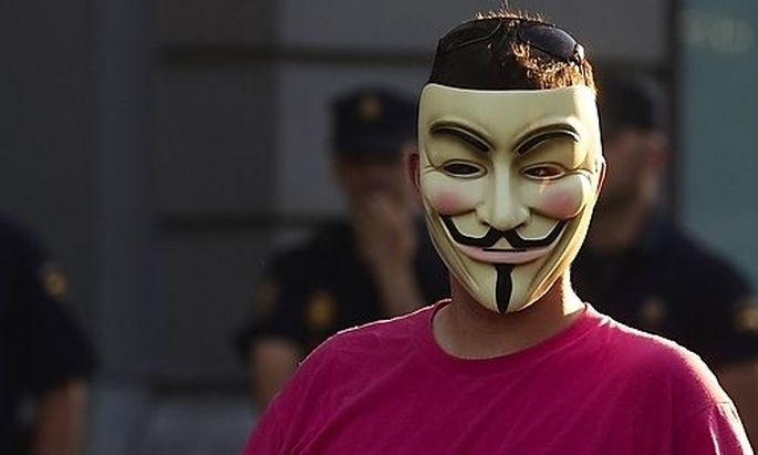A demonstrator wearing an Anonymous group mask attends an assembly against the Euro Pact and the