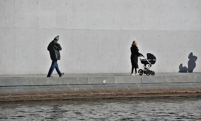 Frau mit Kinderwagen, ein Mann und ein Schattenwurf in einer Stadt Frau mit Kinderwagen vor einer Treppe an einem Fluss