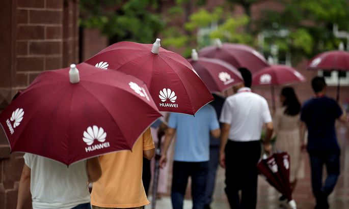 FILE PHOTO: Guests hold umbrellas with Huawei logos in the rain at Songshan Lake New Campus in Dongguan