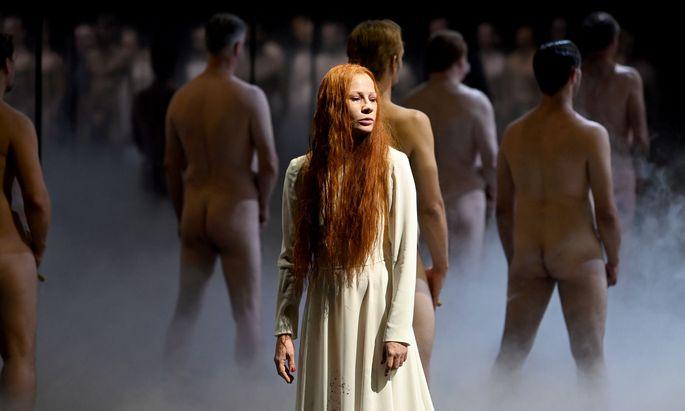 """Eine Königin, die ihren Kopf verliert: Birgit Minichmayr als Titelheldin in Friedrich Schillers """"Maria Stuart"""", umringt von einer Männer-Masse."""