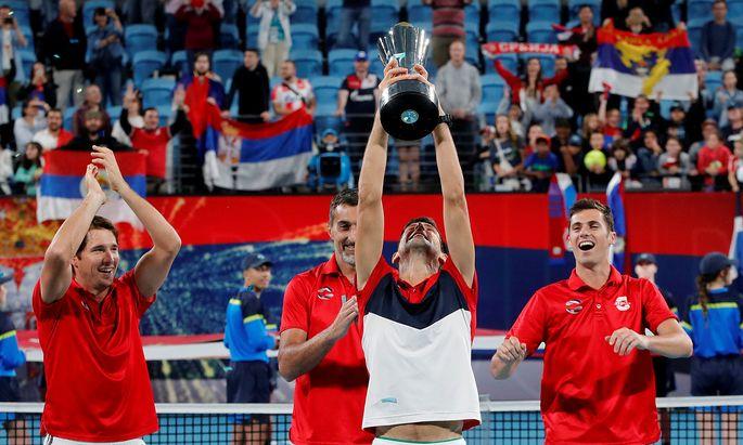 Novak Djokovic jubelt mit Pokal und Kollegen