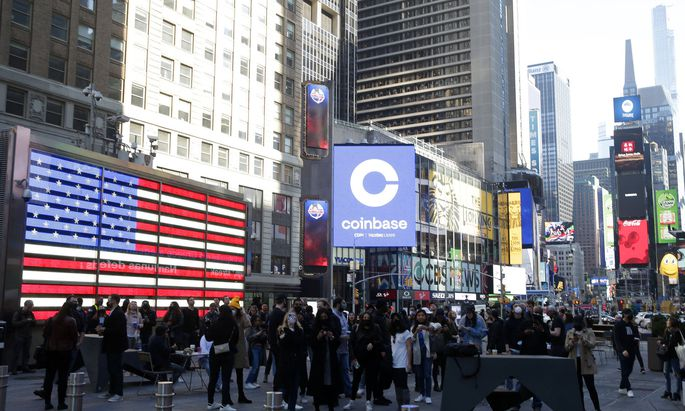 The Coinbase logo is displayed on screens in Times Square when Coinbase Global, Inc. beings trading under the symbol CO