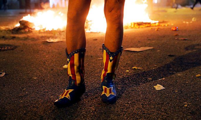 Ein Demonstrant trägt bei einem Protest Stiefel mit der katalanischen Separatisten-Flagge (Barcelona, 15. 10. 2019).