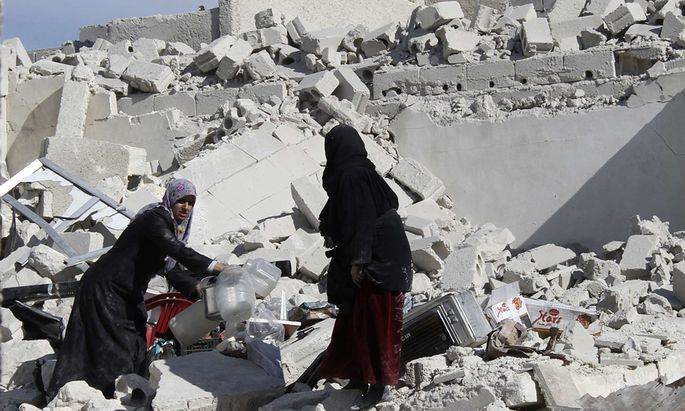 Women hold plastic bottles as they stand amid rubble of damaged buildings at a site in Masaken Hanano in Aleppo