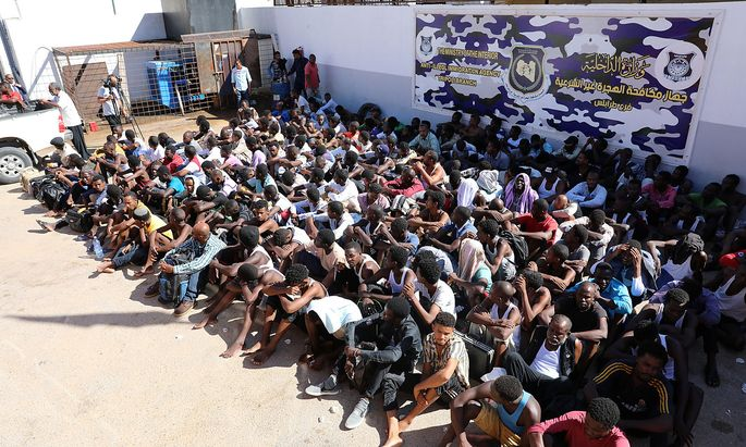 Sudanese migrants sit at a detention center before their voluntary return to their country, in Tripoli