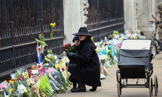 Menschen versammeln sich vor dem Buckingham Palace in London und legen Blumen nieder.