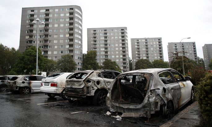 Burned cars are pictured at Frolunda Square in Gothenburg