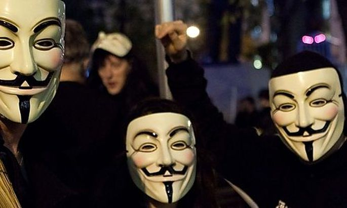 Occupy Wall Street protestors wearing Guy Fawkes masks commonly associated with the hacker group Anon