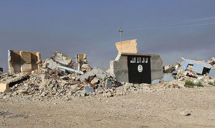 Symbolbild: Eine Flagge, wie sie häufig von der der Terrororganisation IS verwendet wird, auf einem zerstörten Haus im Irak.