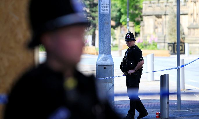 Police officers stand on duty at the cordon surrounding the Manchester Arena in Manchester