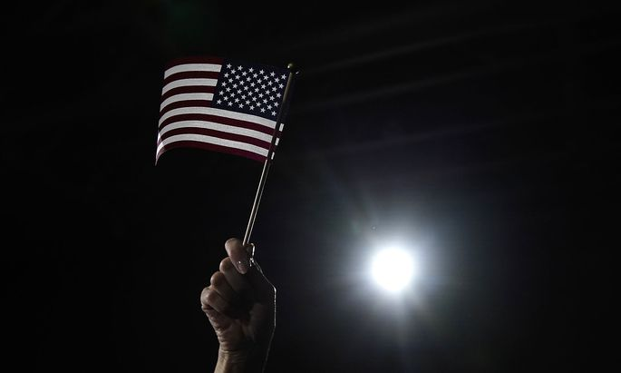 A supporter waves a U.S. flag as Democratic presidential candidate and former South Bend, Indiana Mayor Pete Buttigieg speaks at his rally at Drake University in Des Moines, Iowa, U.S.