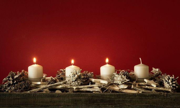 Adventkranz mit drei brennenden Kerzen.