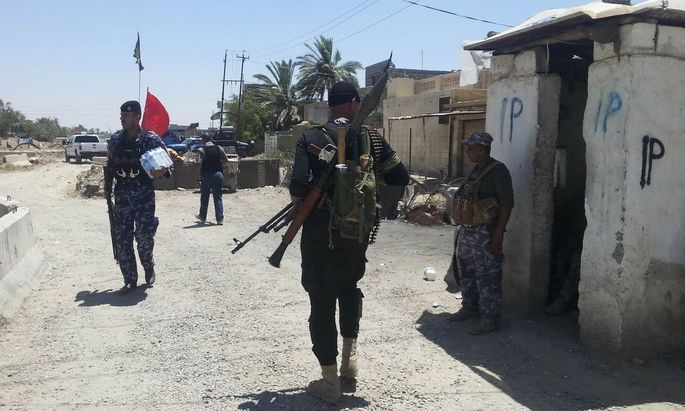 Members of the Iraqi security forces take part in an intensive security deployment at a checkpoint in the city of Baquba