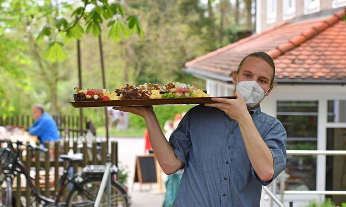 Ein Kellner traegt ein Tablett mit bayerischen Schmankerl,Speisen zu den Tischen-er traegt einen ffp2 Mundschutz,Maske.